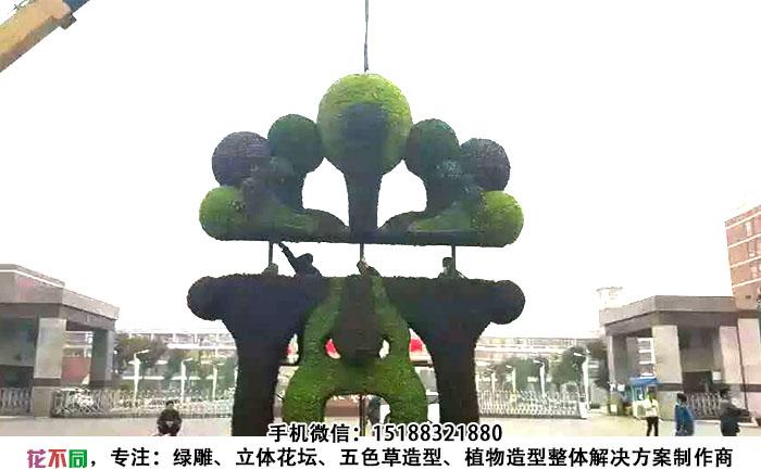 吊车正在吊装四川成都脸谱五色草造型雕塑